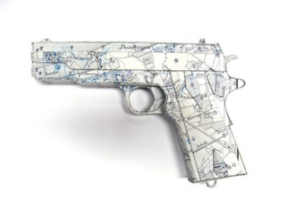 "Photo of Ken Kalman's sculpture ""Colt 45."" Artwork depicts a gun made of maps."
