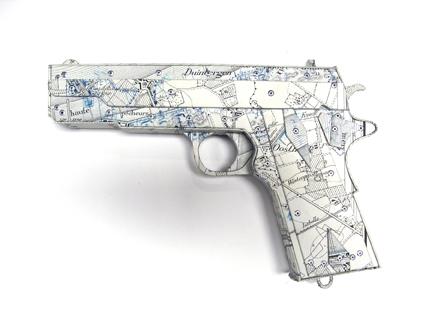 """Photo of Ken Kalman's sculpture """"Colt 45."""" Artwork depicts a gun made of maps."""