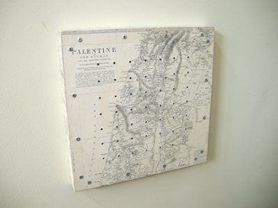 """Photo of Ken kalman's sculpture """"Counting the Omar.""""  Artwork depicts a map of Palestine with holes and pegs."""