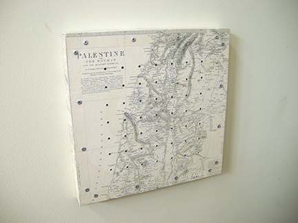 "Photo of Ken kalman's sculpture ""Counting the Omar."" Artwork depicts a map of Palestine with holes and pegs."