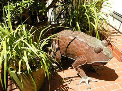"Photo of Ken Kalman's sculpture ""Frog.""  Artwork depicts a copper frog."