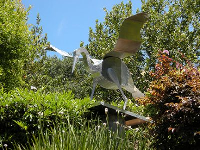 "Photo of Ken Kalman's sculpture ""Great Blue Heron."" Artwork depicts an aluminum heron, wings outstretched."
