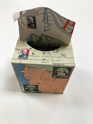 """Photo of Ken Kalman's sculpture """"Nope"""". Artwork depicts a tissue box made of maps with some images of President Trump in homage to Shepard Fairey's """"Hope."""""""