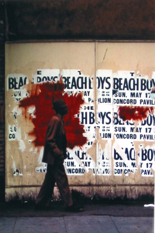 """Photo of Richard Nagler's photograph """"Beach Boys."""" Artwork depicts a man walking in front of plywood that has partially shredded Beach Boys concert street posters on it. Wall and posters have been defaced with red paint."""