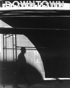 """Photo of Richard Nagler's photograph """"Downtown in Black & White.""""  Artwork depicts a man walking under scaffolding  with a sign """"Downtown"""" at the top. In black and white with lots of shadows."""