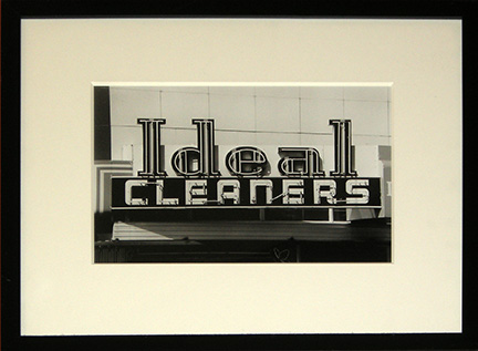 """Photo of Richard Nagler's photograph """"Ideal Cleaners."""" Artwork depicts the Ideal Cleaners neon store sign in black and white."""
