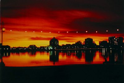"""Photo of Richard Nagler's photograph """"Sunset at Lake Merritt."""" Artwork depicts Lake Merritt with buildings along the edge and in reflection.  Colors are black with the sky deep red, yellow and orange."""