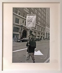 """Photo of Richard Nagler's photograph """"Make America Think Again!""""  Artwork depicts a young man walking down the street carrying the sign """"Make America Think Again!"""""""