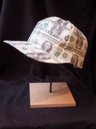 """Phot of Ray Beldner's sculpture """"Tasty"""" (After Jenny Holzer's Truisms: Money Creates Taste). The artwork depicts a baseball cap made out of U.S. currency."""