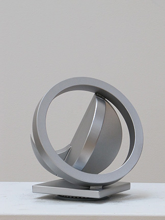 """Photo of Fletcher Benton's study for a sculpture """"Folded Circle Ring Maquette No. 110."""" Artwork depicts silver metal folded circle balanced with a silver ring."""