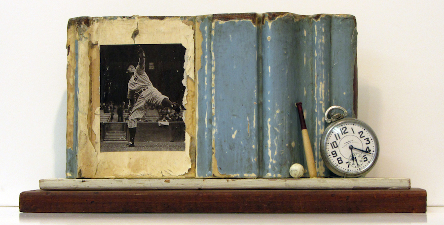 "Photo of Stacey Carter's assemblage sculpture ""Yankee Pitch."" Artwork depicts a shelf with blue partial frame, a photo of a baseball pitcher, a small ball and bat and a watch."