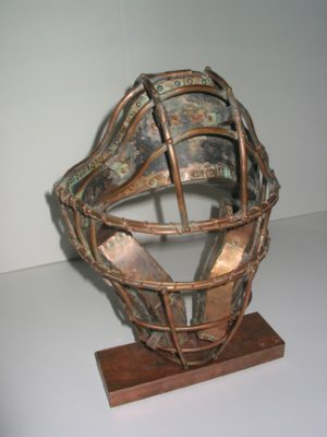 "Photo of Ken Kalman's sculpture ""Catcher's Mask."" Artwork depicts a baseball catcher's mask made of copper."