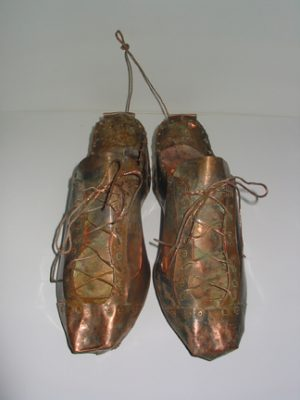 "Photo of Ken Kalman's sculpture ""Baseball Cleats."" Artwork depicts baseball cleats made of copper."