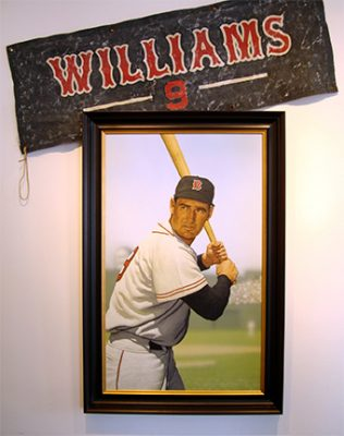 """Photo of Arthur K. Miller's painting """"Ted Williams at Fenway."""" Artwork depicts Williams at bat. A separate banner is angled above the painting."""