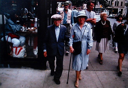 """Photo of Richard Nagler's photograph """"Homage to Raphael Soyer, NYC, September 1987."""" Artwork depicts people walking on a busy city street, man and a woman with a cane at center."""