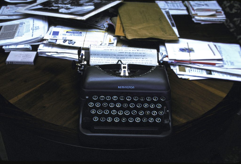 """Richard Nagler's photograph """"Isaac's Typewriter, Miami Beach July 1990."""" Artwork depicts a Remington typewriter on a table. Papers and letter cover much of the table surface."""
