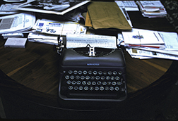 "Richard Nagler's photograph ""Isaac's Typewriter, Miami Beach July 1990."" Artwork depicts a Remington typewriter on a table. Papers and letter cover much of the table surface."