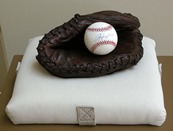 "Photo of Richard Newman's sculpture ""Seasons Slide by Faster Now."" Artwork depicts a baseball glove on a base."