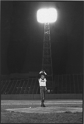 "Photo of Roberto Salas's photograph ""Castro Pitching, La Habana 1965, 2:30 am."" Artwork depicts Fidel Castro arms raised about to pitch a baseball under bright stadium lights."