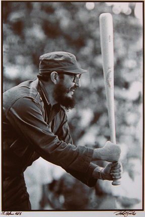 "Photo of Roberto Salas's photograph ""Castro with Bat, La Habana."" Artwork depicts a smiling Fidel Castro with a baseball bat ready to take a swing."