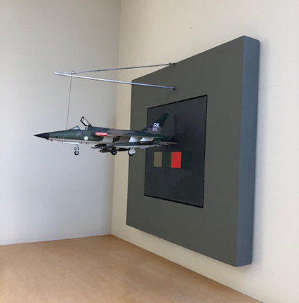 """Photo of Fletcher Benton's assemblage """"Aircraft: F105D-Jet."""". Artwork depicts a jet plane in front of a background."""