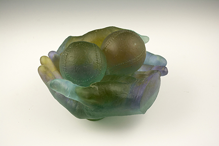 "Photo of Milt Friedly's cast crystal sculpture ""Coveted Foul Ball -2."" Artwork depicts two hands cradling two baseballs."