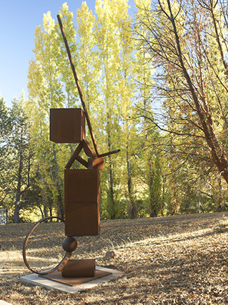 """Photograph of Fletcher Benton's sculpture """"Blocks on Blocks: One on Two, Ball on Ring."""" Image depicts a large scale steel sculpture outside by trees. Sculpture is a vertical arrangement of blocks, tubes, a ring and a ball."""
