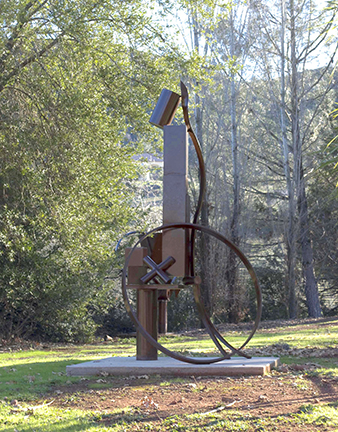 """Photograph of Fletcher Benton's sculpture """"One-Legged Table-Stacked Boxes."""" Image depicts a large scale steel sculpture outside by trees. Sculpture is a vertical arrangement of boxes, tubes, a table surface, a ring and an """"x""""."""