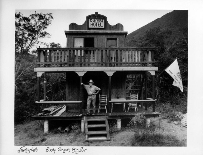 "Photo of Chris Felver's gelatin silver print ""Bixby Canyon, Big Sur."" Image depicts Lawrence Ferlinghetti on the porch of a wooden building with the sign ""Old West Hotel."" Signed by Lawrence Ferlinghetti."