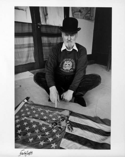 "Photo of Chris Felver's gelatin silver print ""Ferlinghetti with Flag."" Image depicts Lawrence Ferlinghetti wearing bowler hat and sitting cross legged on the floor pointing at a flag. Signed by Lawrence Ferlinghetti."