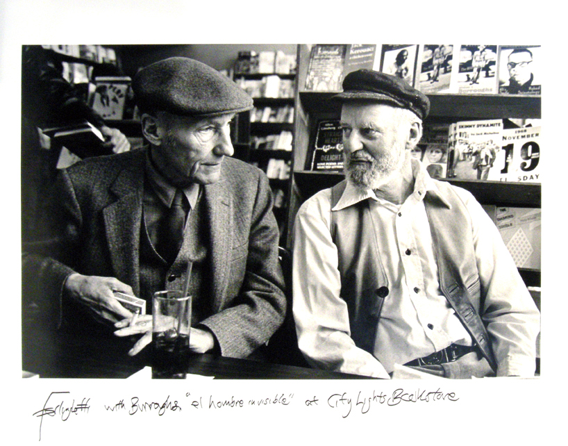 "Photo of Chris Felver's gelatin silver print ""Ferlinghetti with Burroughs at City Lights."" Image depicts both men, wearing caps, sitting next to each other with bookshelves in the background. Signed by Ferlinghetti."
