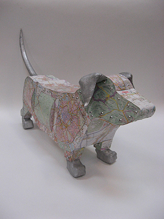 """Photo of Ken Kalman's sculpture """"Dachshund."""" Image depicts a metal dauchshund dog with a map image surface."""