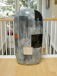 """Photo of Jun Kaneko's ceramic sculpture """"Untitled, Dango."""" Image depicts a grey monolith with a rounded top. Background color is grey with squares of color and groupings of black drips."""